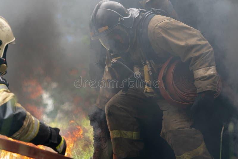 Пожарная команда федеральной пожарной службы во время огня - тушащ, тренируя для того чтобы преодолевать зону огня психологическо стоковая фотография
