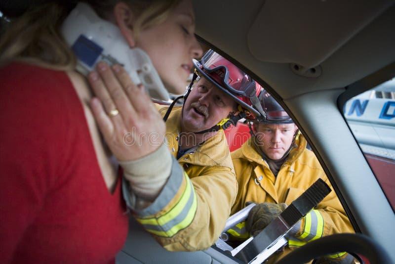 пожарные автомобиля помогая поврежденной женщине стоковые изображения
