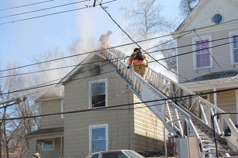 Пожарные воюя огонь дома стоковое изображение rf