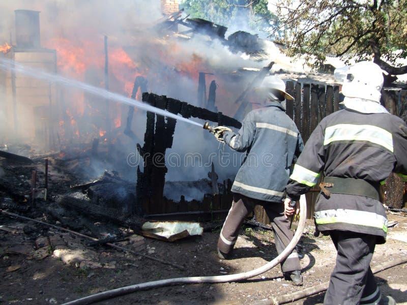 Пожарные воды пожарного распыляя тушат пожар в apar стоковые фото