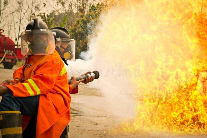 Пожарные в огне бой действия во время тренировки стоковое фото rf