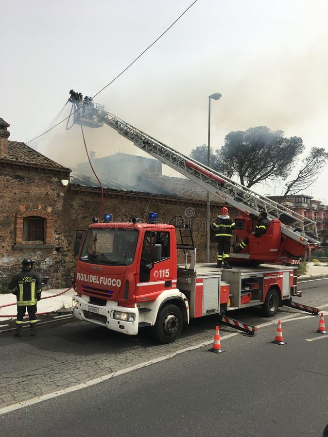 Пожарные занятый для того чтобы потушить огонь в старом доме стоковые фотографии rf