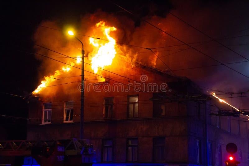 Пожарные направляют поток воды на горящем доме строить полностью ад пылать, и бой пожарного для того чтобы получить управление fl стоковая фотография