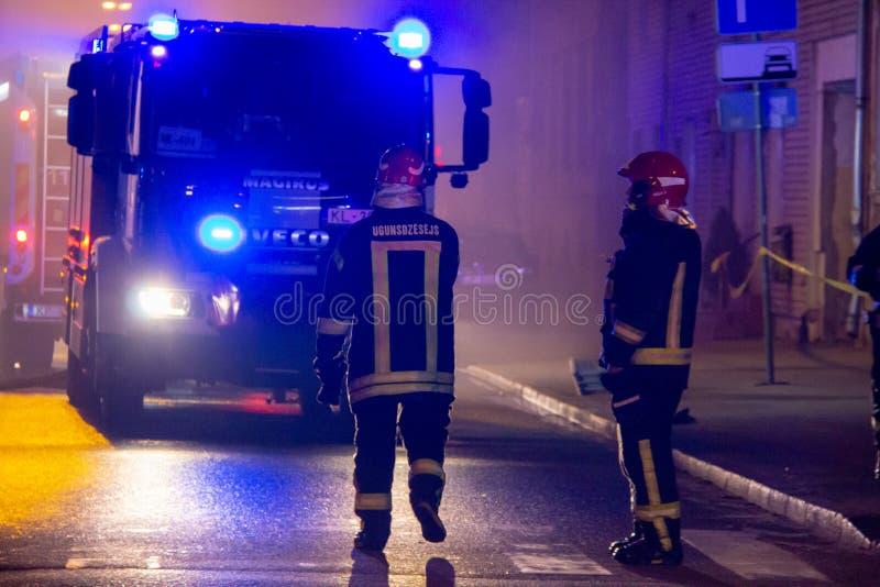 Пожарные направляют поток воды на горящем доме строить полностью ад пылать, и бой пожарного для того чтобы получить управление fl стоковое фото rf