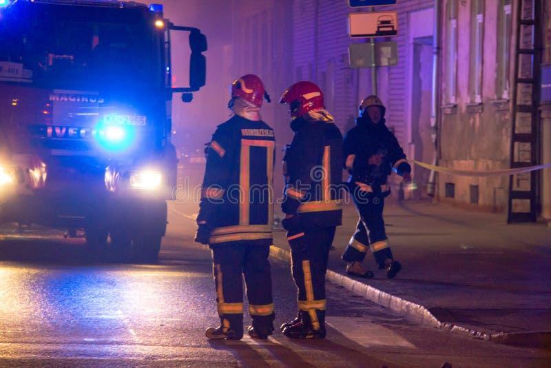 Пожарные направляют поток воды на горящем доме строить полностью ад пылать, и бой пожарного для того чтобы получить управление fl стоковое изображение rf