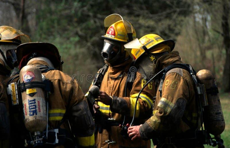 Пожарные принимая перерыв после боя огня дома в Bowie, Мэриленде стоковое изображение