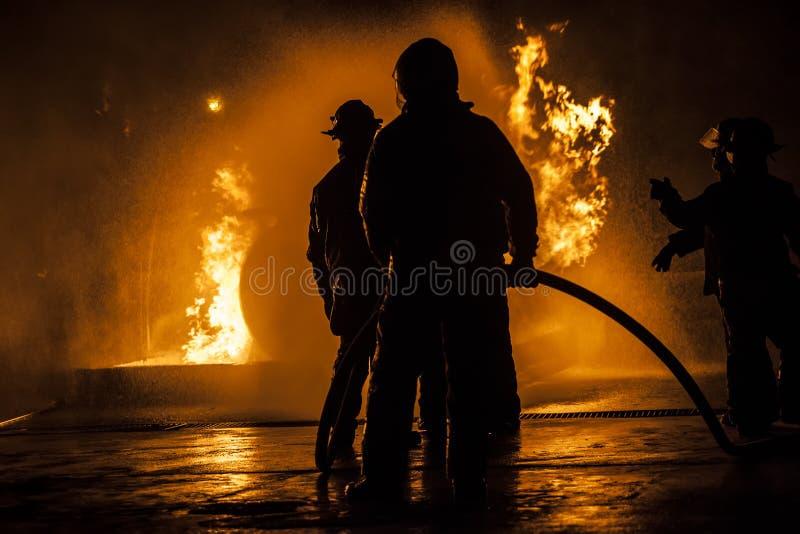 Пожарные стоя в линии воюя огонь стоковое изображение