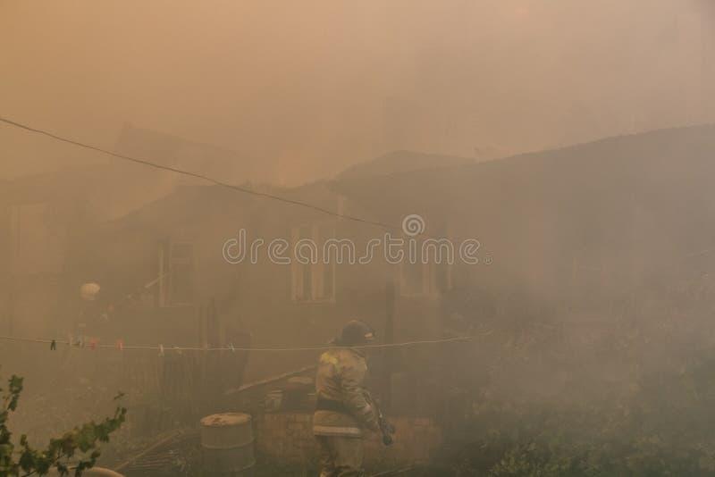 Пожарные тушат большой огонь дома в дыме стоковые фото