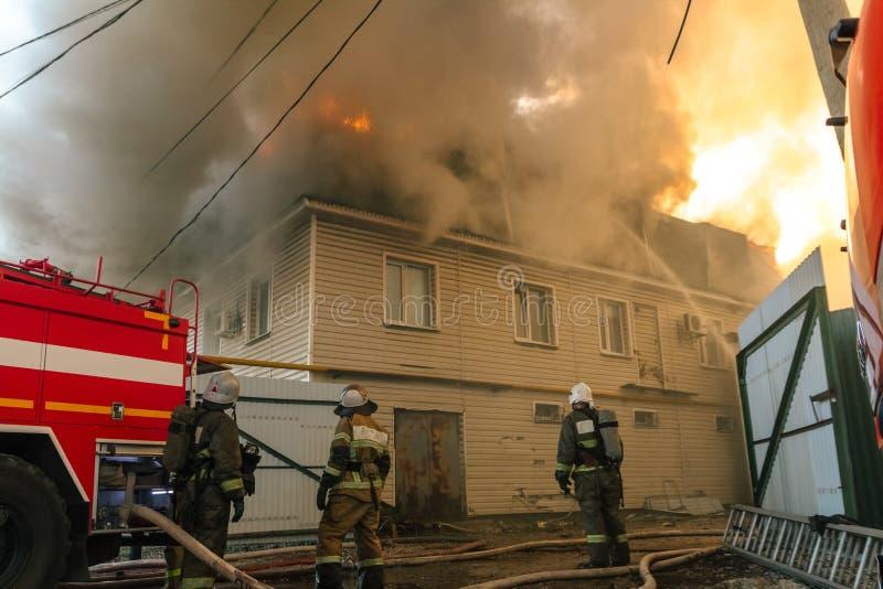 Пожарные тушат большой огонь дома в дыме стоковое изображение