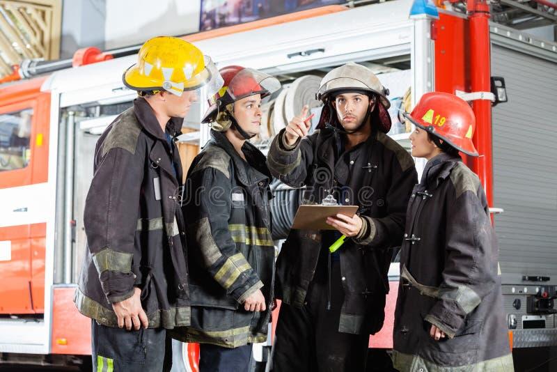Пожарный показывая что-то к коллегам на стоковая фотография