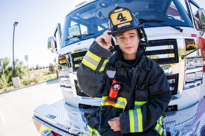 Пожарный представляя перед автомобилем стоковые фотографии rf