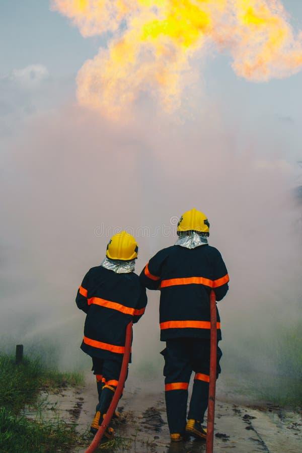 Пожарный распыляя высокую воду давления к огню стоковые фотографии rf