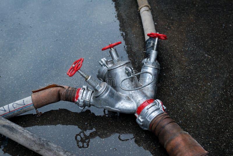 Пожарный рукав и тройник для воды на том основании стоковые фото
