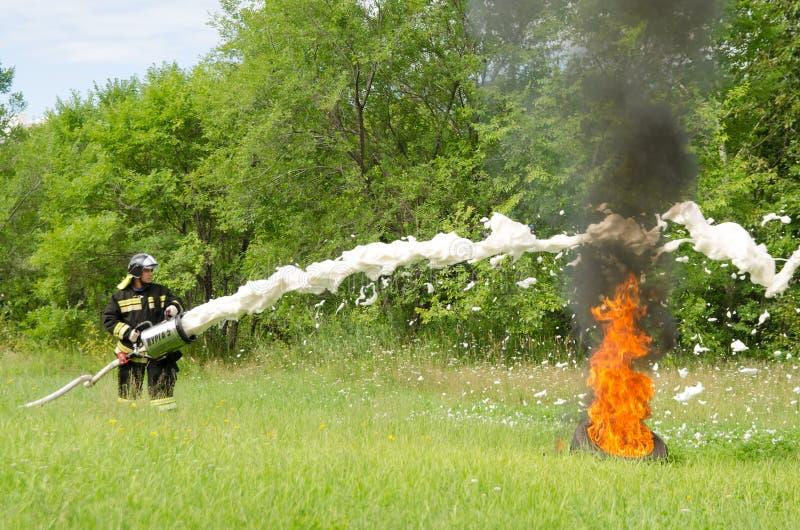 Пожарный тушит горящую автошину во время perfo демонстрации стоковые изображения rf