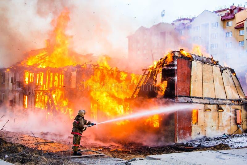 Пожарный тушит огонь стоковая фотография rf