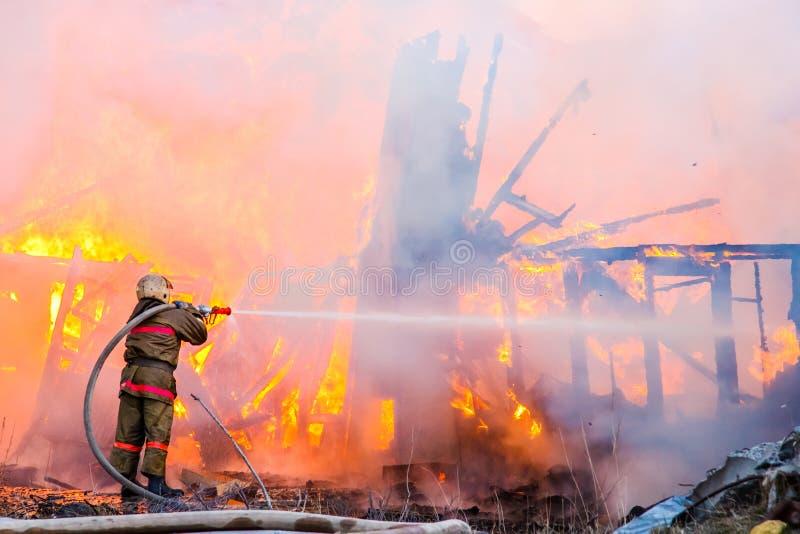 Пожарный тушит огонь стоковое фото