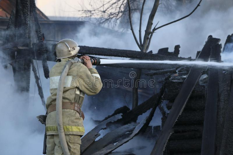 Пожарный тушит огонь E стоковая фотография