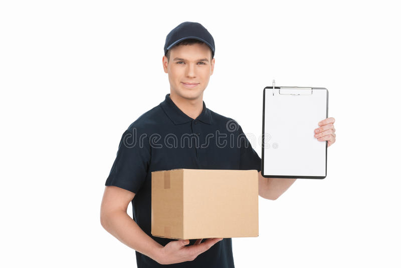 Пожалуйста подпишите здесь для того чтобы получить вашу коробку. Жизнерадостный молодой hol работника доставляющего покупки на дом стоковое изображение
