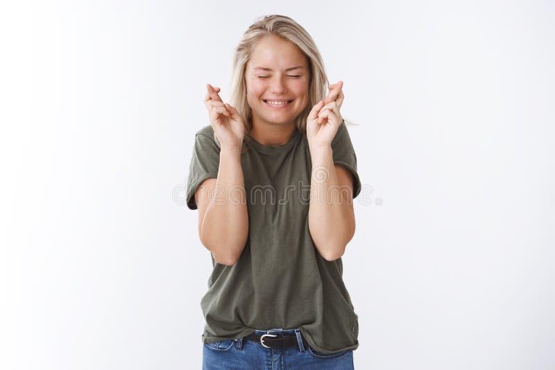 Пожелайте мне везение Возбужденная оптимистическая привлекательная женщина надеется сегодня парень для того чтобы сделать пальцы  стоковое изображение