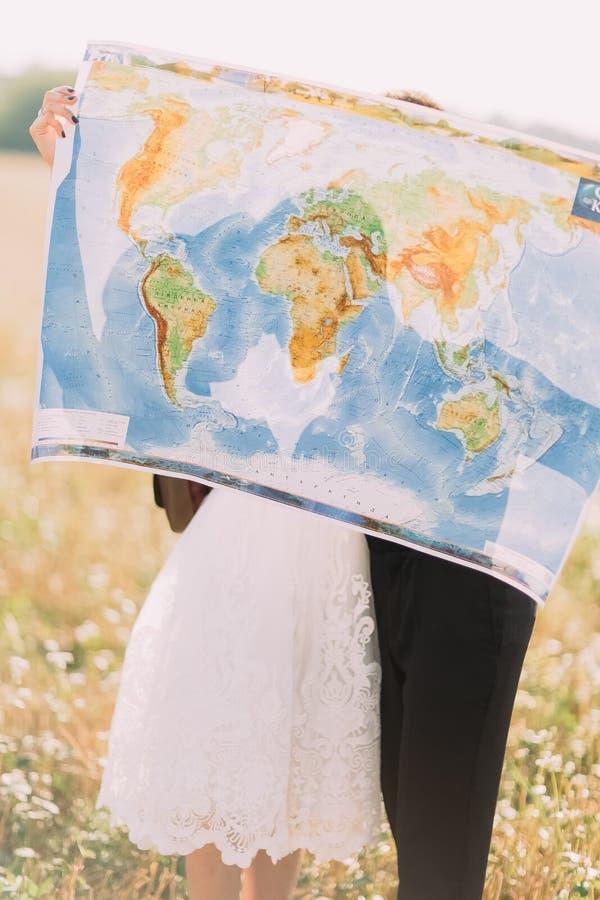 Пожененный портрет конца-вверх справедливой держащ карту мира закрывая их стороны на предпосылке солнечного поля стоковое фото rf