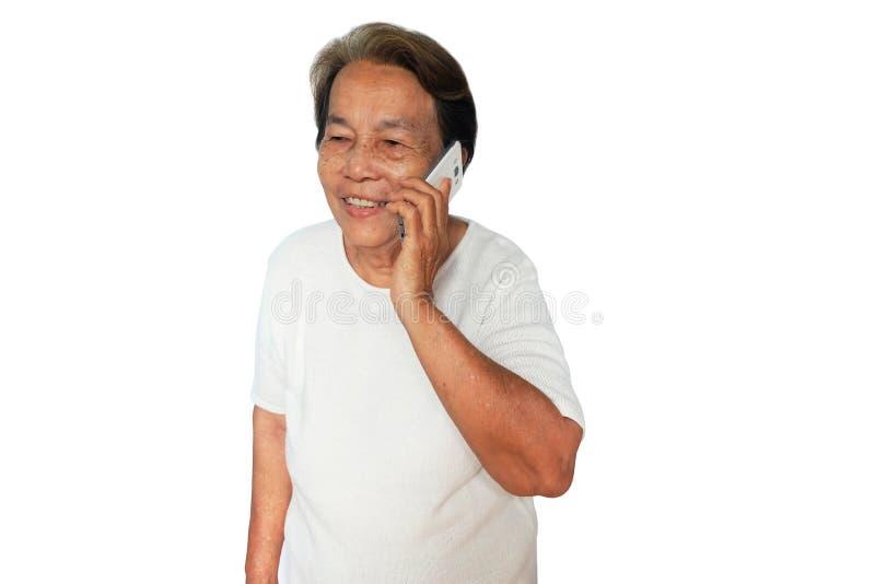 Пожилая азиатская женщина использует мобильный телефон с улыбкой изолированный на белизне стоковая фотография rf
