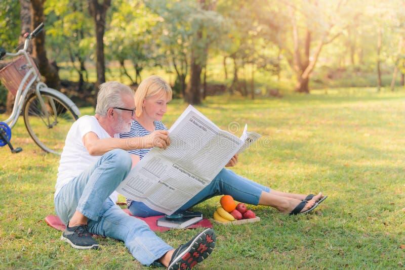 Пожилая газета чтения пар в саде на заходе солнца Любовь пар концепции старшая стоковые изображения rf