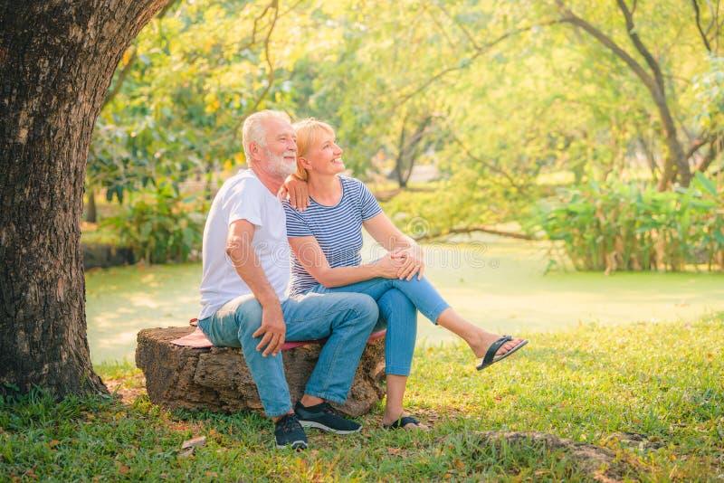 Пожилая газета чтения пар в саде на заходе солнца Любовь пар концепции старшая стоковая фотография rf