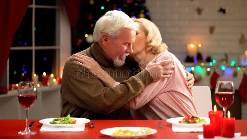 Пожилая дама нежно целуя супруга, признательного для подарка рождества, единения стоковые изображения