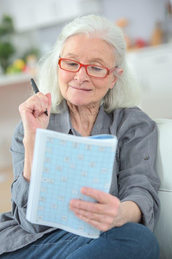 Пожилая дама озадачивая над викториной кассеты стоковая фотография rf