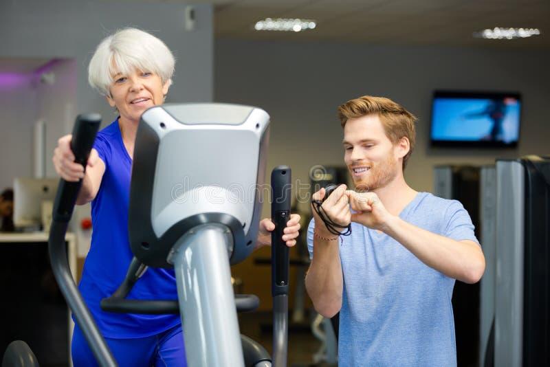 Пожилая дама разрабатывая с дружелюбным молодым мужским тренером стоковые изображения rf