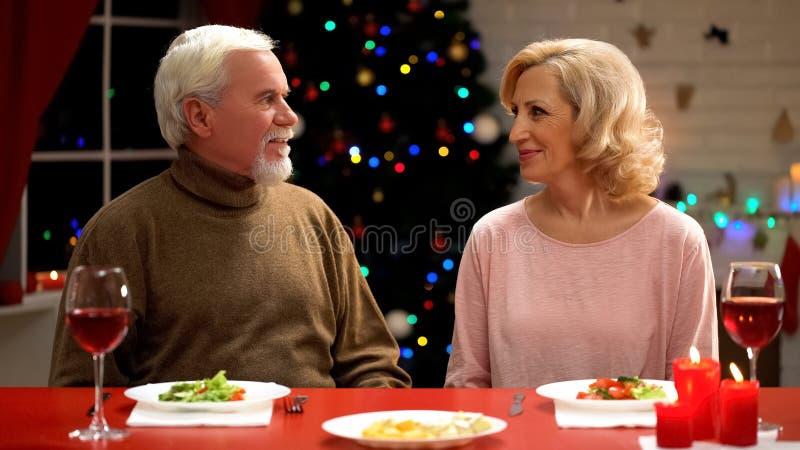 Пожилая жена и супруг сидя на таблице, встречая Новый Год совместно, праздник стоковые изображения rf