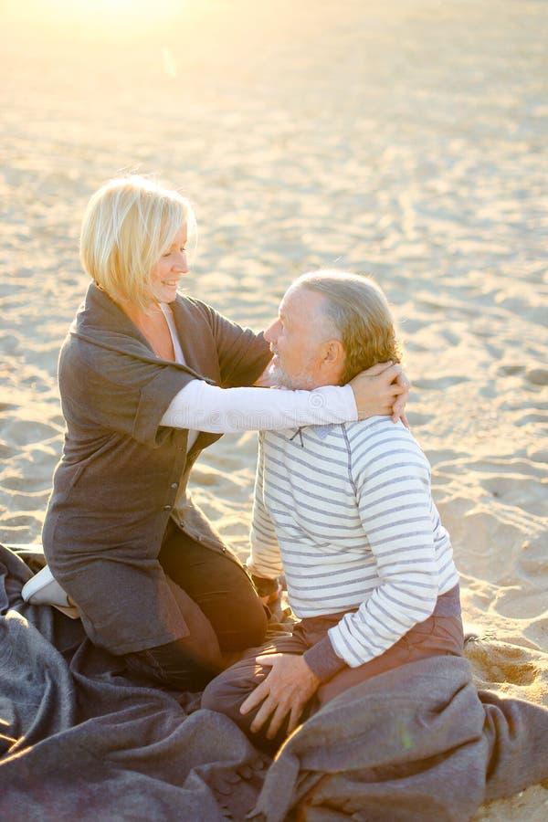 Пожилая жена обнимая старшего супруга и сидя на шотландке на пляже песка в лучах солнца стоковое изображение rf