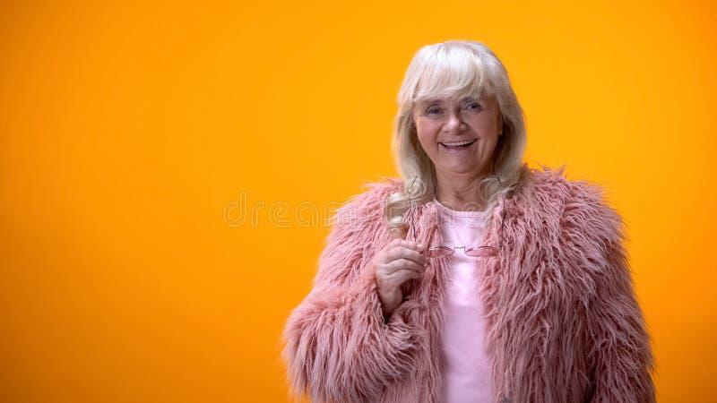 Пожилая женщина в розовом пальто держа солнечные очки и усмехаясь к ка стоковое фото
