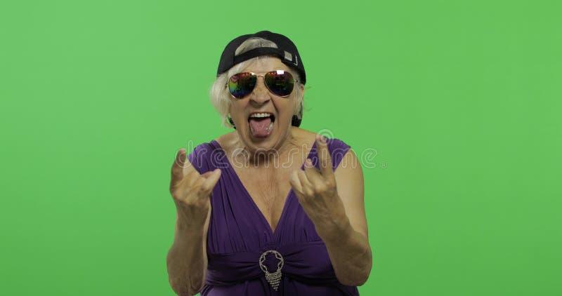 Пожилая женщина в солнечных очках кричит с улыбкой и язык показывать o стоковые фото