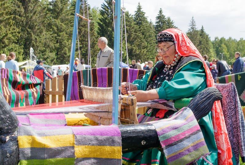 Пожилая женщина в Bashkir одеждах усажена на старое деревянное oom и соткет ковер Национальный праздник Sabantuy в парке города стоковое изображение