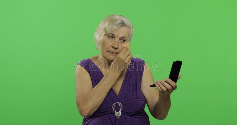 Пожилая женщина делает макияж Старая милая бабушка o стоковые фотографии rf