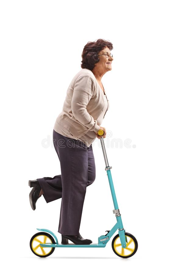 Пожилая женщина ехать самокат стоковые фото