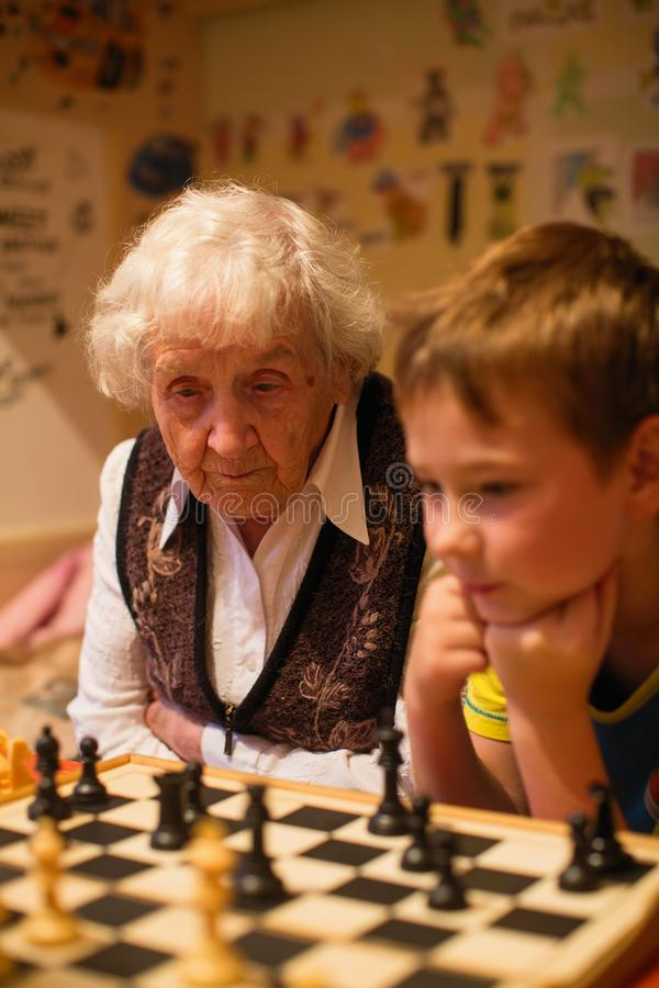 Пожилая женщина играет шахматы с ее маленьким внуком r стоковое изображение rf