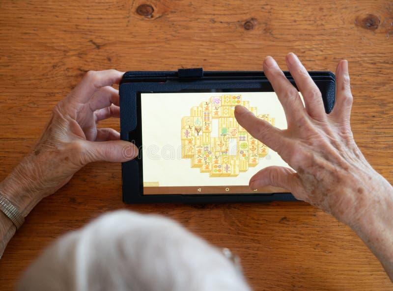 Пожилая женщина играя Mahjongg с ее руками и частью ее он стоковые изображения rf