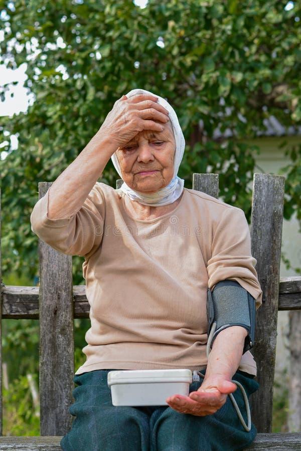 Пожилая женщина измеряет кровяное давление концепция медицины, возраста, здравоохранения и людей - женщина старшего возраста с то стоковое фото
