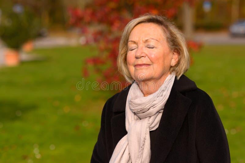 Пожилая женщина наслаждаясь мирным моментом стоковая фотография rf