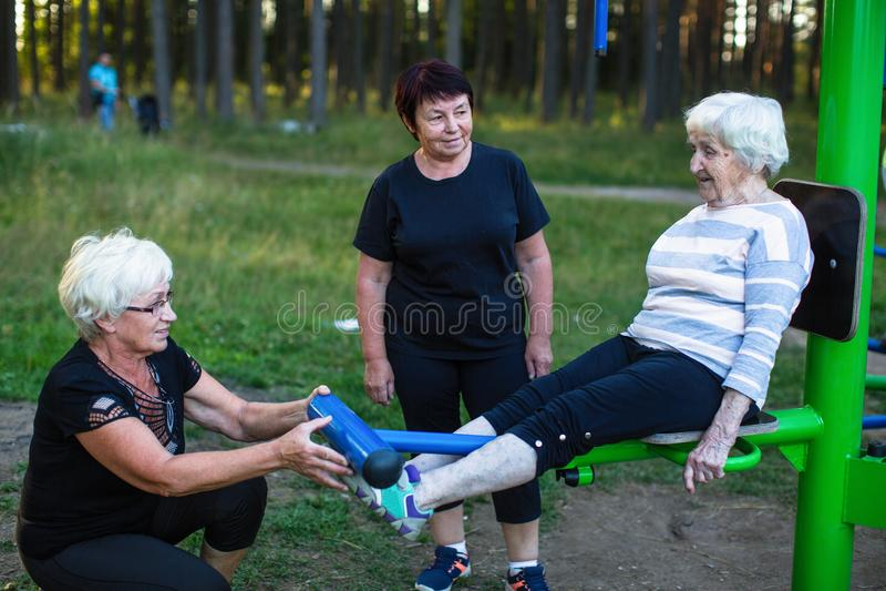 Пожилая женщина на имитаторе спорт в парке, 2 взрослых женщины помогает ей сделать тренировки Спорт стоковые изображения