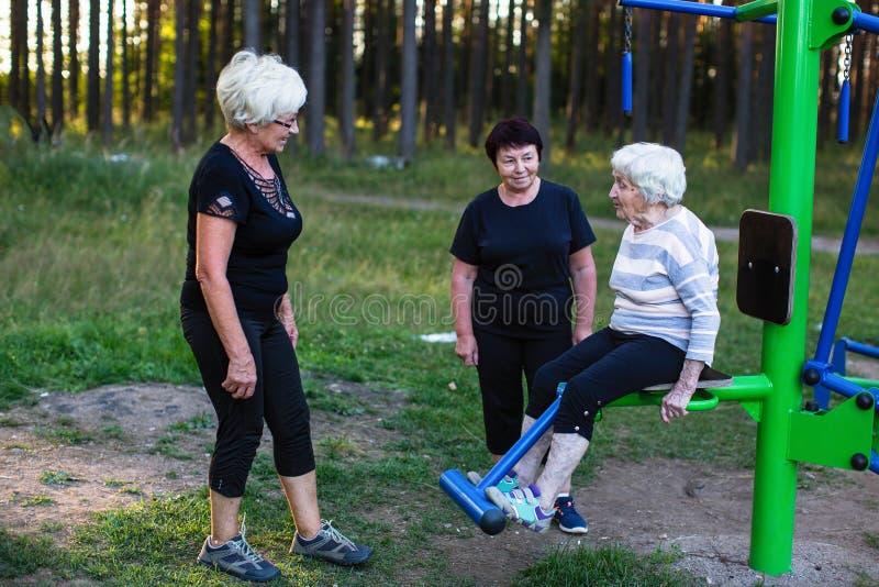 Пожилая женщина на имитаторе спорт, 2 женщины помогает ей сделать тренировки Помощь стоковые изображения rf