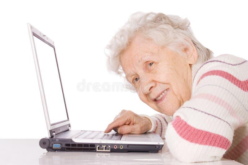 Пожилая женщина на компьютере стоковое фото