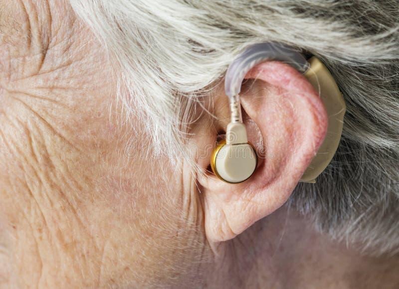 Пожилая женщина нося аппарат для тугоухих стоковая фотография rf