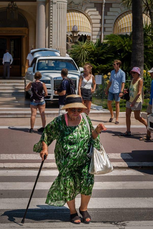 Пожилая женщина пересекает бульвар перед гостиницой Carlton, Канн стоковая фотография