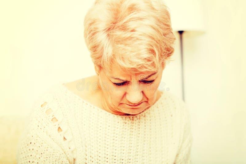 Пожилая женщина при депрессия сидя на кресле стоковая фотография