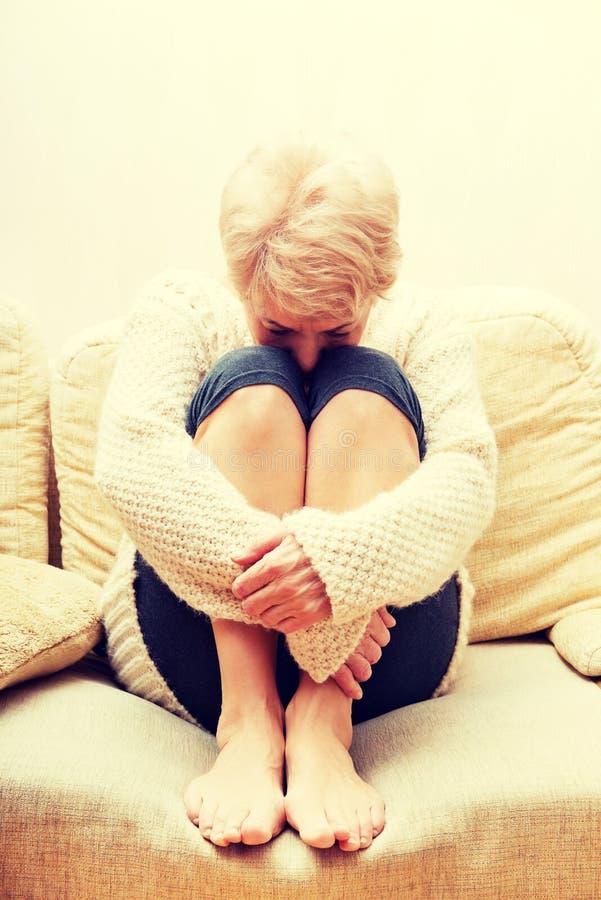 Пожилая женщина при депрессия сидя на кресле стоковые изображения