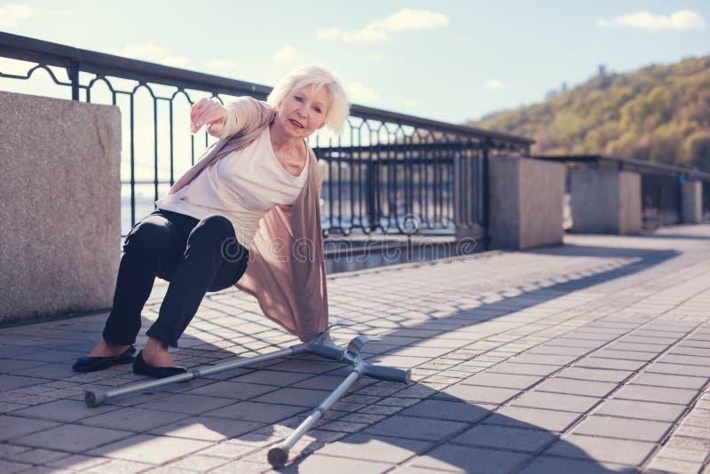 Пожилая женщина пробуя получить вверх после падать вниз стоковое изображение rf