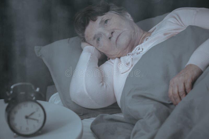 Пожилая женщина пробуя спать стоковое изображение rf